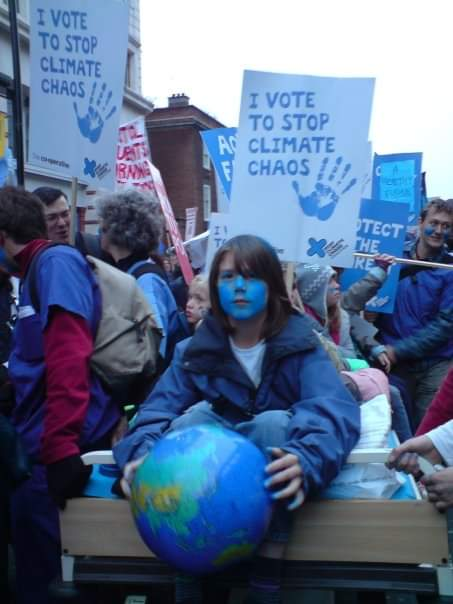 A protest march in London. You can only just see the tops of houses over the tide of people. A boy in blue sits on a bed being pushed through the streets. He is surrounded by adults wearing blue. They are waving banners of white and blue saying things like 'I Vote to Stop Climate Chaos'. The boy is in the centre holding a globe, face painted blue. He looks directly at the camera. His eyes challenge us to act.