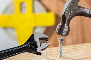 hammering a nail into wood, yellow background