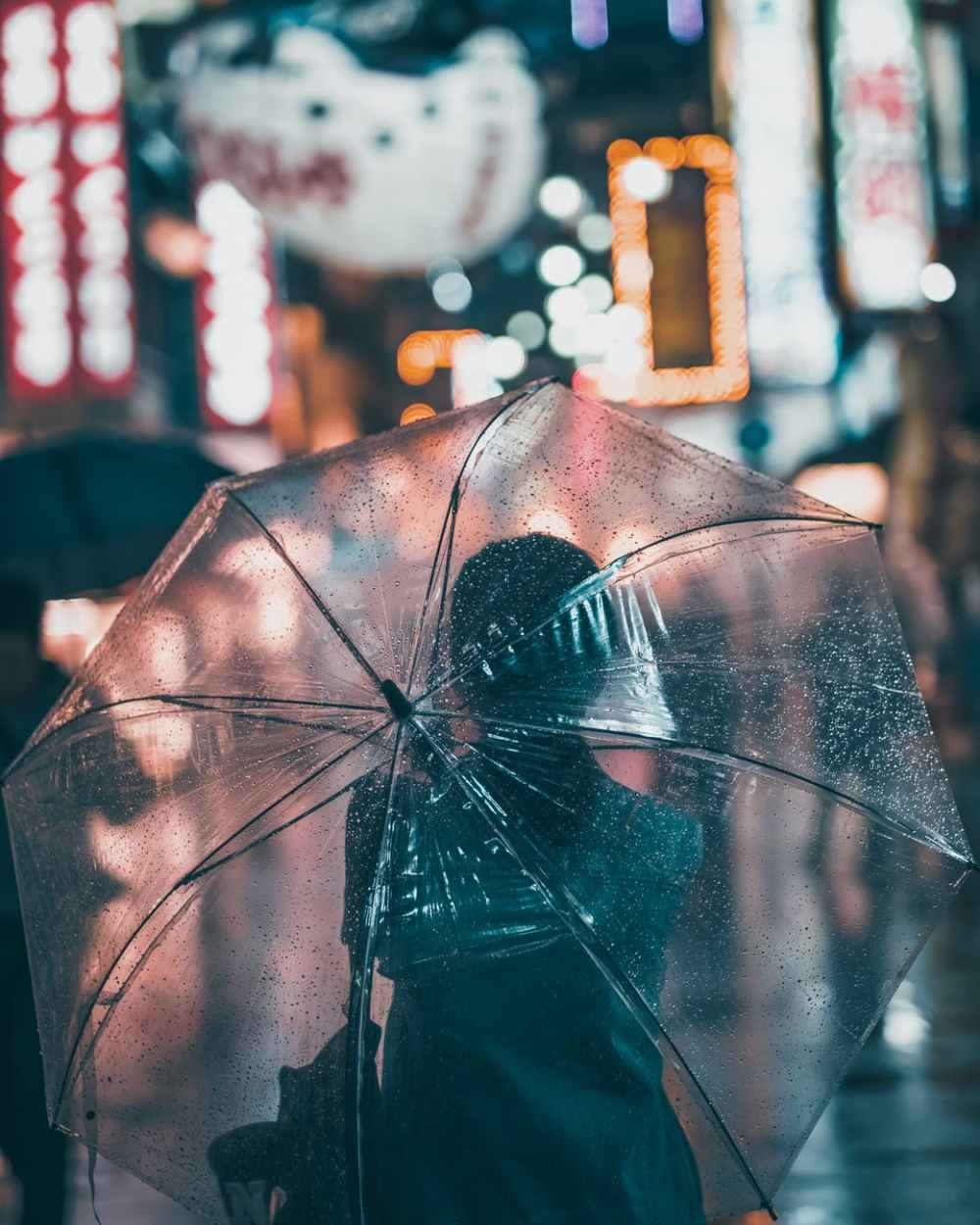 the back of a woman under a transparent wet umbrella on a city street at night