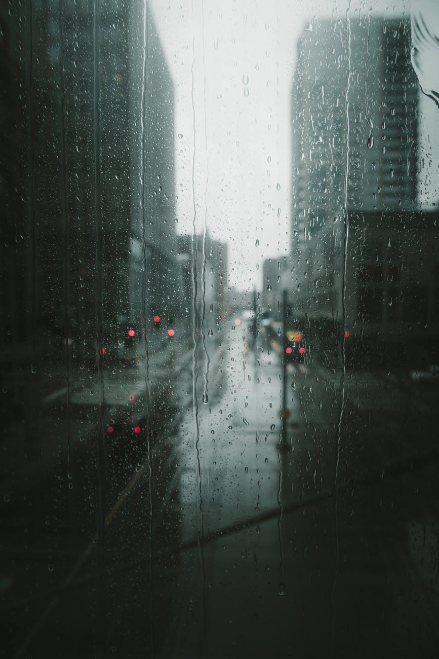 Rainy, grey city street through a wet window